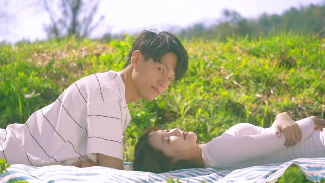 korean man and woman lying on the grass field - 年の差カップル点の映像素材/bロール