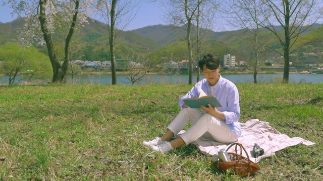 korean man reading a book on the grass field - 年の差カップル点の映像素材/bロール