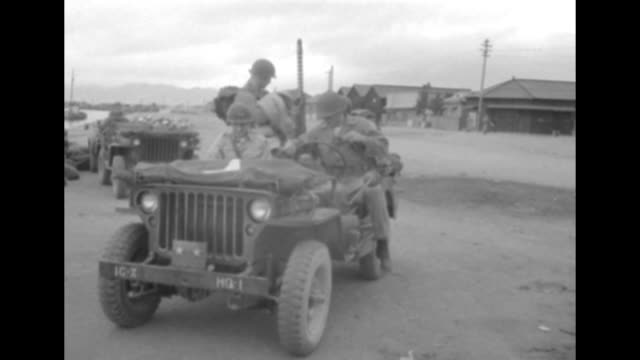 VS Korean man speaks as US GI with rifle and goggles looks on / officers depart in jeep / US troop train approaches belching black smoke as people...
