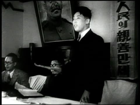 Korean men at long table one standing talking Joseph Stalin painting BG WS Korean Communists Government in session meeting Russia Korea flag BG CU...