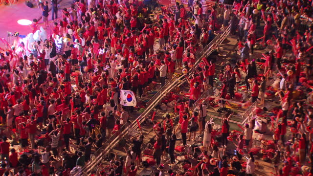 Korean soccer fans watching performance and cheering for national soccer team at Gwanghwamun Square