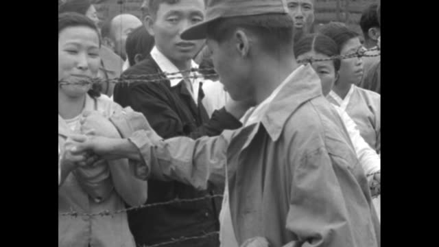 Korean soldier standing at barbed wire fence wipes his eyes / he holds hands with young woman standing on other side of fence / VS they hold hands /...