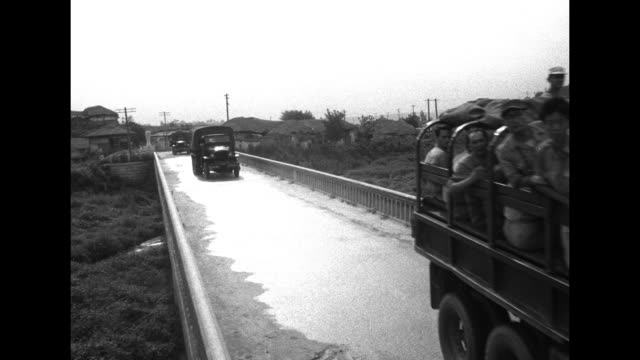 Korean soldier stands in road watching convoy of army trucks jeeps loaded with soldiers cross bridge / VS convoy along road in village / civilians...