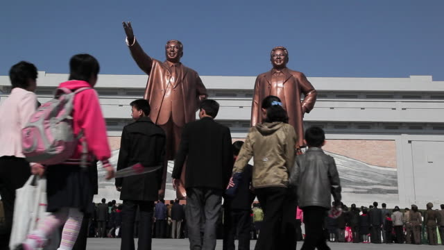 korean tourists stop to look at the statues of former presidents kim il-sung and kim jong il at the mansudae grand monument near the mansudae assembly hall on mansu hill in pyongyang, north korea. - north korea stock videos & royalty-free footage
