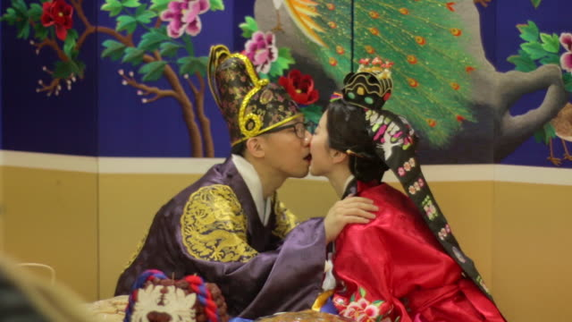 korean traditional bride and groom passing a jujube with their mouths (korean post wedding custom called pyebaek) - korea stock-videos und b-roll-filmmaterial