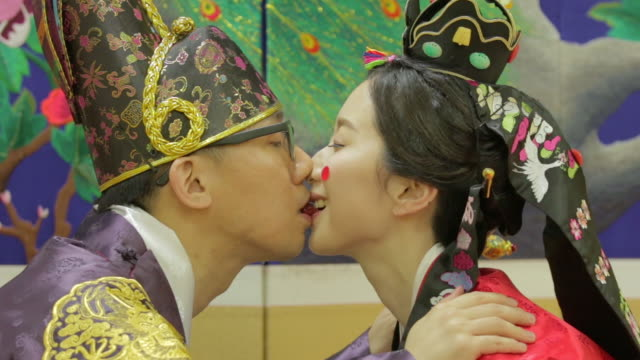 Korean traditional bride and groom passing a jujube with their mouths (Korean post wedding custom called Pyebaek)