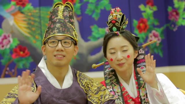 korean traditional bride and groom waving hands and kissing (korean post wedding custom called pyebaek) - zungenkuss stock-videos und b-roll-filmmaterial