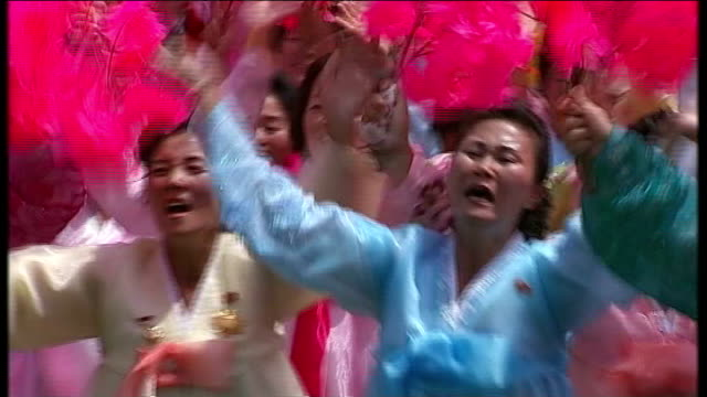 korean war 60th anniversary military parade in pyongyang soldiers marching along troops marching along camera operator next to speakers female band... - 北朝鮮点の映像素材/bロール