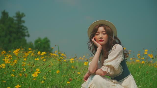 vídeos y material grabado en eventos de stock de korean woman sitting on the cosmos flower field in jeju island, korea - mano en la barbilla