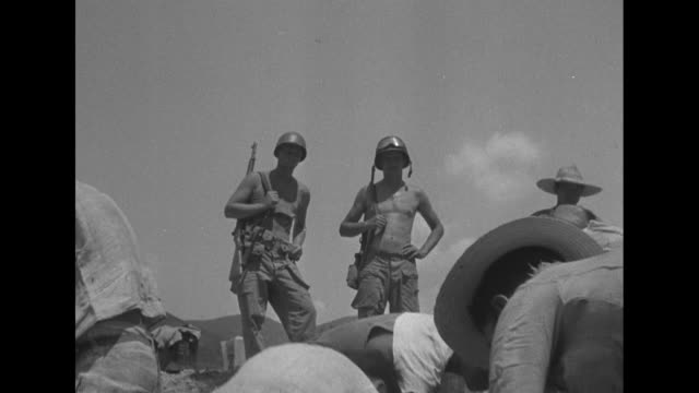 korean workers standing around next to airfield / shot from behind two us soldiers of korean workers repairing airfield / vs korean workers repairing... - 朝鮮戦争点の映像素材/bロール