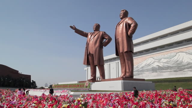 koreans pay respect to the statues of former presidents kim il-sung and kim jong il at the mansudae grand monument near the mansudae assembly hall on mansu hill in pyongyang, north korea. - north korea stock videos & royalty-free footage