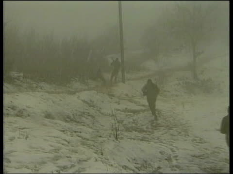 LIB YUGOSLAVIA Kosovo EXT SNOWING BV Soldiers from foxhole and away across snowy field PAN NOT SNOWING Soldiers away down alleyway