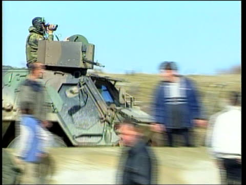 stockvideo's en b-roll-footage met kosovo orahovac ext ms kfor jeep towards past kfor soldiers on duty at side of road cms german kfor soldier checking man's car pull out ms side and... - kosovo