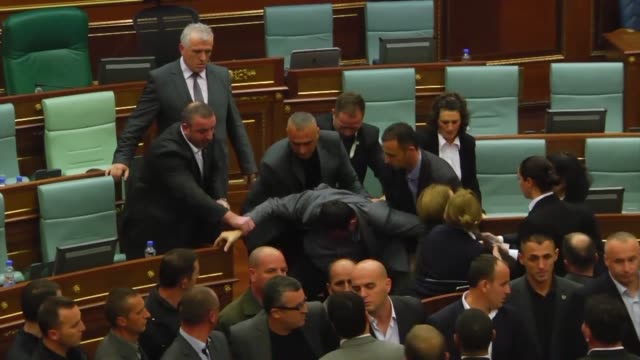 Kosovo parliamentary lawmakers step back as tear gas fills the chamber at Kosovo's parliament in Pristina on October 23 2015 after being released by...