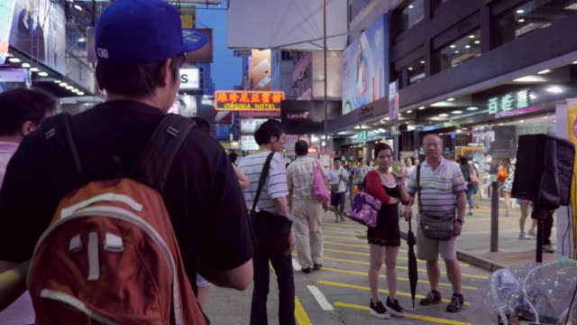 kowloon street market with tourists and locals at night - nachtmarkt stock-videos und b-roll-filmmaterial