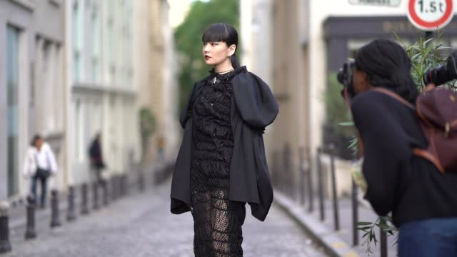 kozue akimoto wears a black lace mesh dress with ruffles and puff sleeves, outside cdg comme des garçons, during paris fashion week - womenswear... - lace textile stock videos & royalty-free footage