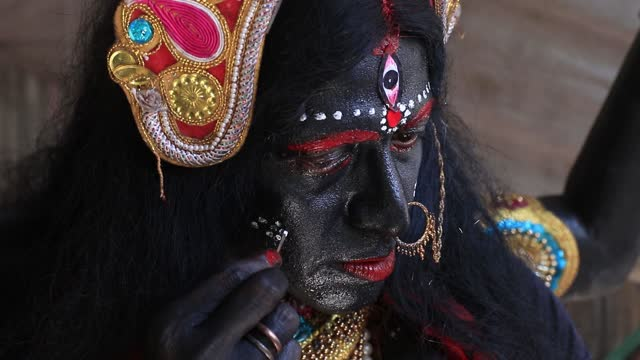 krishna bairagi a bahurupi artist make up ready to dressed as hindu goddess kali hold the covid-19 awareness hold the placard on the street and apple... - high street stock-videos und b-roll-filmmaterial