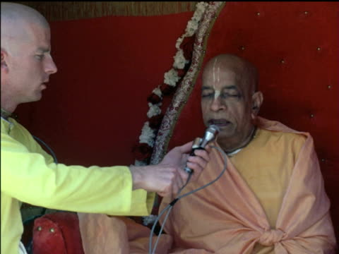 / krishna sect swami sri bhaktivedanta prabhupada talking to his followers from colorful throne disciples listening religiously hare krishna sect on... - apostle stock videos and b-roll footage