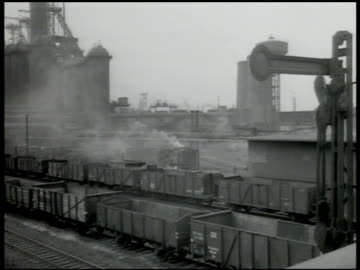 vidéos et rushes de krupp steel factory w/ smokestacks smoking. railroad coal cars in factory yard. worker pushing ladle of molten metal, workers helping pour hot metal... - ruhr