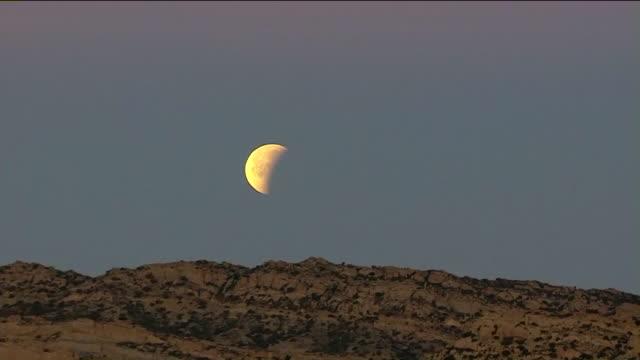 aerial view of super blue blood moon ascending above a ridge in the san fernando valley. - rymd och astronomi bildbanksvideor och videomaterial från bakom kulisserna