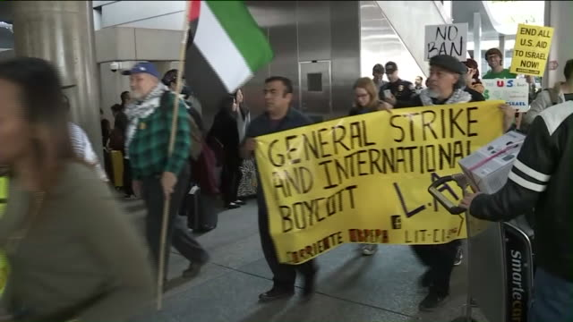 Demonstrators chanted marched and temporarily blocked both the departures and arrivals area of the Tom Bradley International Terminal at Los Angeles...