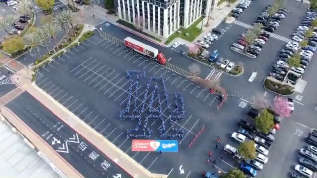 """drone pov employees at the smart final in commerce showed their spirit by making a human """"la"""" sign on opening day - baseballmannschaft stock-videos und b-roll-filmmaterial"""