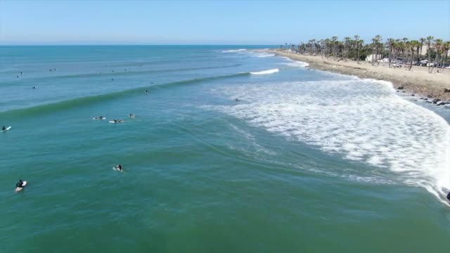 drone povpeople surfing at ventura beach - ventura stock videos and b-roll footage