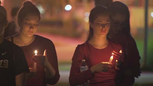 florida community grieves at vigil after marjory stoneman douglas high school shooting - trauernder stock-videos und b-roll-filmmaterial