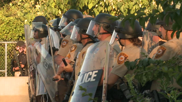 riot police face protesters near a destroyed quick trip after michael brown's death on august 12 2014 in ferguson missouri brown was shot by officers... - police brutality stock videos and b-roll footage