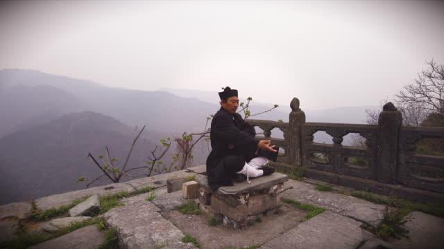 ku fu master wu doing fight meditation on ancient ruins in the wudangshan holy mountains. - カンフー点の映像素材/bロール