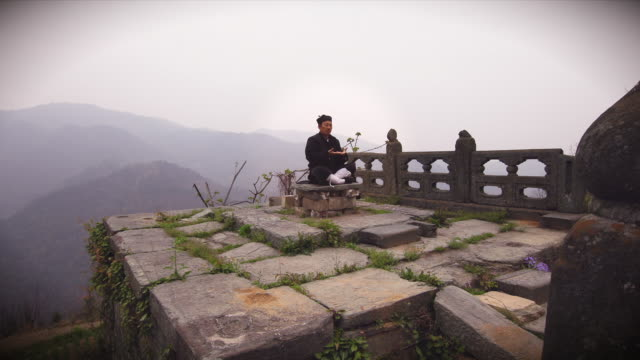 ku fu master wu meditating on ancient ruins with misty wudangshan mountains in the background - カンフー点の映像素材/bロール