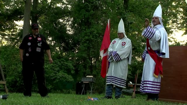 vídeos de stock, filmes e b-roll de ku klux klan meeting and burning of the cross ceremony confederate white knights member speaking to group / holding united nations flag / un flag... - ku klux klan