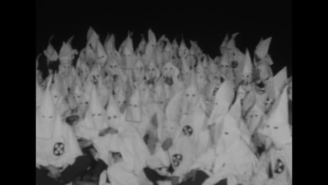 vídeos de stock, filmes e b-roll de ku klux klan members parade through city streets on way to stone mountain for animal ceremonies / the ceremony starts at midnight with the burning of... - ku klux klan