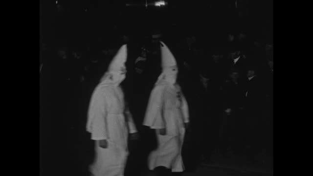vídeos de stock, filmes e b-roll de vs ku klux klansmen march at night in robes and hoods hiding their identities and carrying an american flag / ms two klansmen lead horse also in robe... - ku klux klan