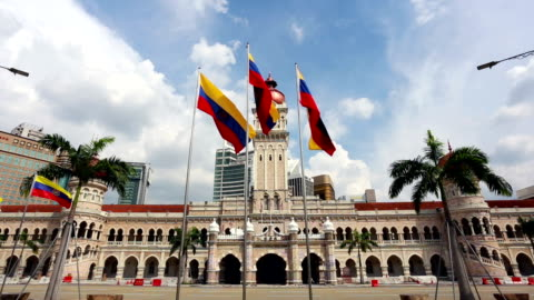 kuala lumpur city flags in front of the ultan abdul samad building in malaysia capital city. - clock tower stock videos & royalty-free footage