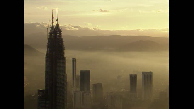 ws kuala lumpur cityscape and petronas towers in mist; 1996 - petronas twin towers stock videos & royalty-free footage