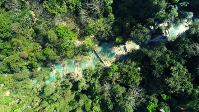 kuang si waterfall famous landmark nature travel place of luang prabang city, laos. bird eye view landscape. - purity stock videos & royalty-free footage