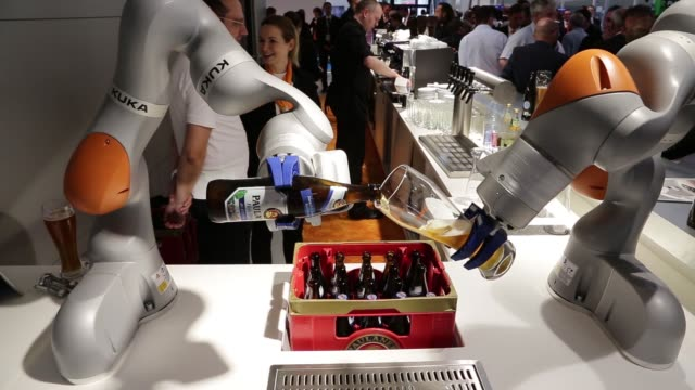 A Kuka LBR iiwa industrial robotic arm pours a glass of weiss beer during a display on the Kuka AG exhibition stand during the Automatica trade fair...