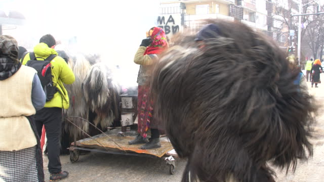 Kukeri And Other Costumed Bulgarians Dancing And Singing During A Traditional Kukeri Festival