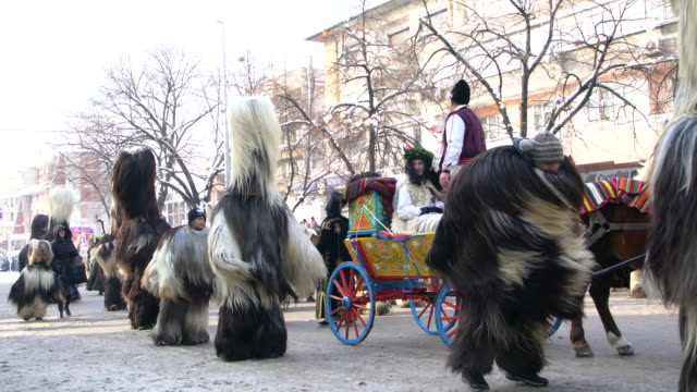 kukeri and other costumed bulgarians marching in procession during a traditional kukeri festival - traditional dancing stock videos and b-roll footage