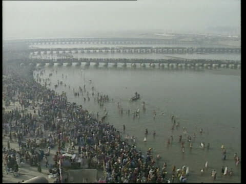vídeos de stock e filmes b-roll de allahabad crowd of hindu pilgrims away to cross bridge over ganges on day before most sacred day of kumbh mela festival gv pilgrims along bridges... - encontrar