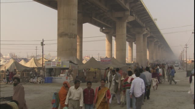 Kumbh Mela pilgrims living under road bridge respond to call to prayer, Allahabad, Uttar Pradesh, India