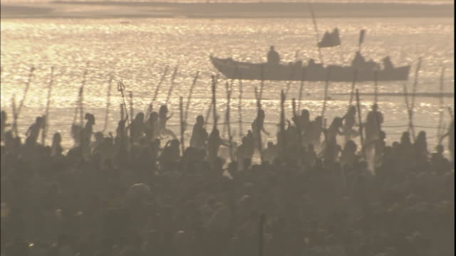 kumbh mela pilgrims run joyfully across banks of ganges, india - pellegrino video stock e b–roll