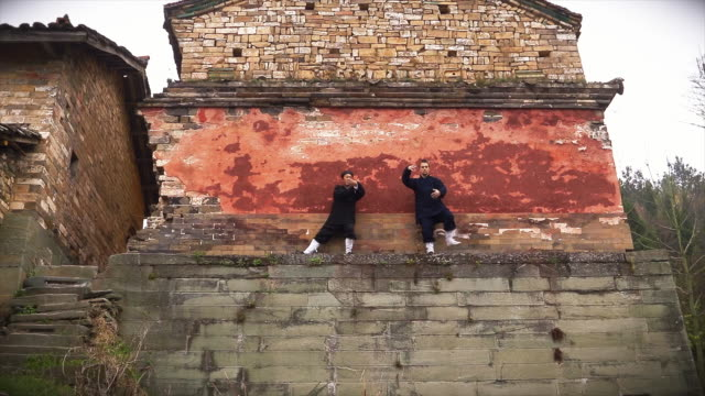 kung fu master wu and his western disciple from dragongate kung fu shool train in front of ancient ruins in the holy wudang shan mountains - apostel bildbanksvideor och videomaterial från bakom kulisserna