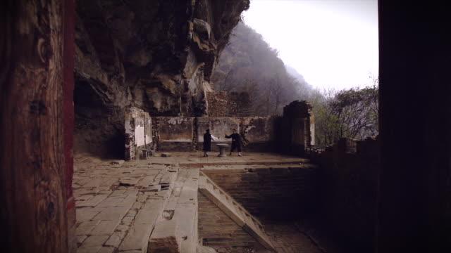 kung fu master wu and his western disciple from dragongate kung fu shool train in ancient ruins in the wudang shan holy mountains. - apostel bildbanksvideor och videomaterial från bakom kulisserna