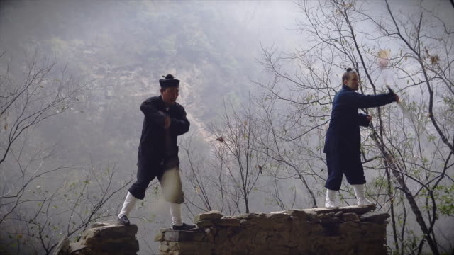 kung fu master wu and his western disciple showing of their skills on ancient wall in wudangshan mountains. - apostle stock videos and b-roll footage
