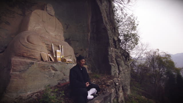 kung fu master wu praying in front of ancient lao tze taoist statue in the holy wudangshan mountains. pan rigth to the misty mountains. - カンフー点の映像素材/bロール