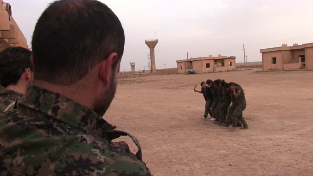 Kurdish People's Protection Unit YPG male and YPJ female fighters dancing traditional Kurdish dance in a military recruitment ceremony in Al Hasakah...