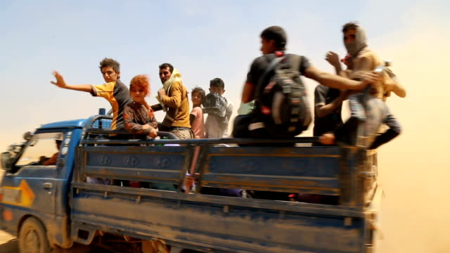 vídeos de stock, filmes e b-roll de kurdish photojournalist meets yazidi refugees travelling from mount sinjar to syria syria yazidi refugees along in open truck through desert people... - curdo