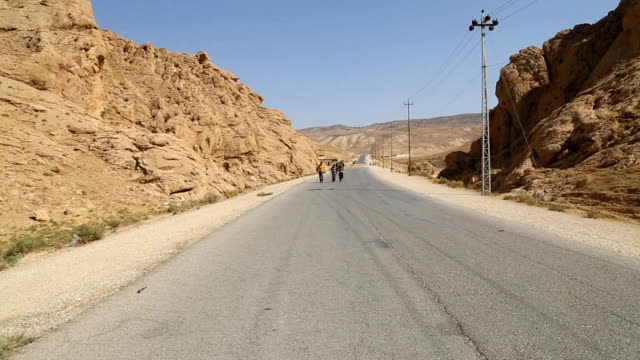 kurdish photojournalist meets yazidi refugees travelling from mount sinjar to syria iraq people along road near mount sinjar with truck past... - ninawa stock videos & royalty-free footage